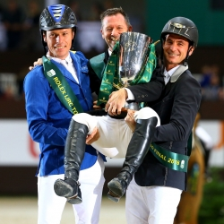 Christian Ahlmann (left) and Steve Guerdat hoist Eric Lamaze