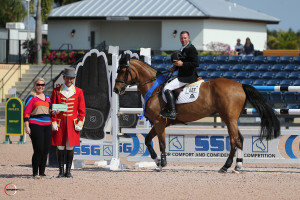 """Eric Lamaze is presented with a $3,000 bonus from Jennifer Ward in the SSG Gloves """"Go Clean for the Green"""" promotion, bringing his total bonus money won to date to $15,000.  Photo by Sportfot"""