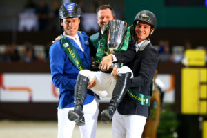Germany's Christian Ahlmann (left) and Switzerland's Steve Guerdat hoist Eric Lamaze holding the Rolex IJRC Top Ten trophy in an impromptu podium celebration.  Photo by Arnd Bronkhorst Photography